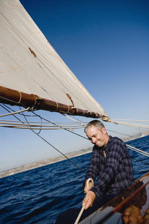 man smiling sitting on a sailing boat LANG_EVOIMAGES
