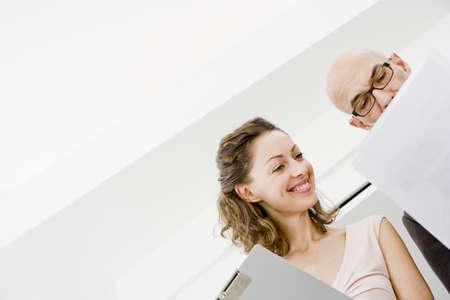 potěšen: 2 podnikatelé studující papíry LANG_EVOIMAGES