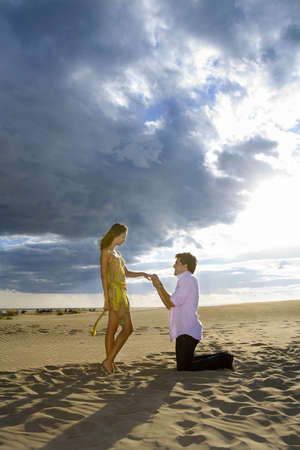 enquiring: Man on knees proposes marriage in sand