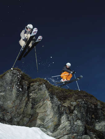 skiers: Skiers jumping over rock