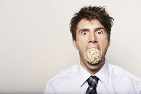Business man with ball in mouth LANG_EVOIMAGES