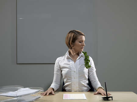 Woman by desk with plant on shoulder