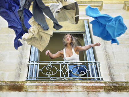 confrontational: Woman throwing clothes by the window