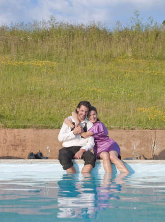 couple sat by swimming pool,embraced