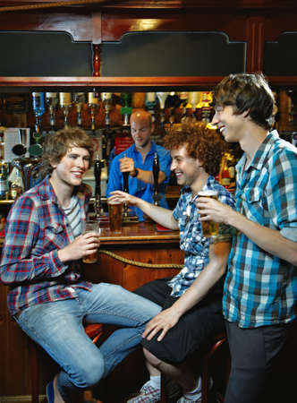 Young men drinking in pub LANG_EVOIMAGES