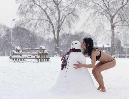out of context: Woman in bikini kissing snowman