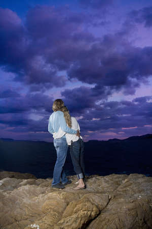 couple look out to sky on rock