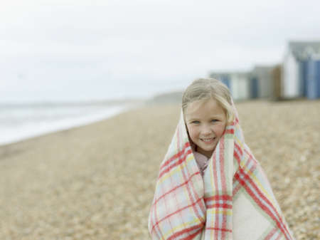 enclose: young Girl huddled in Blanket on Beach