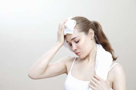 Woman dabbing sweat with towel
