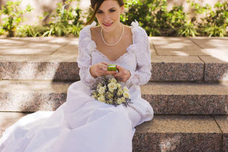 Bride with mobile phone before wedding