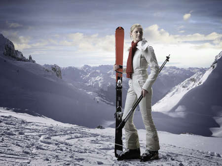 Woman carrying skis on snowy slope