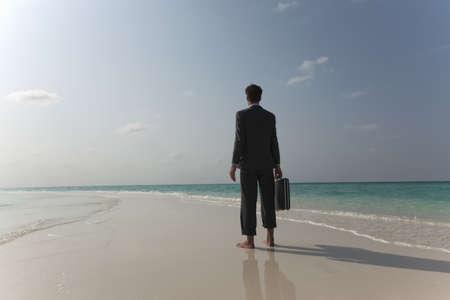endlessly: Businessman walking on tropical beach