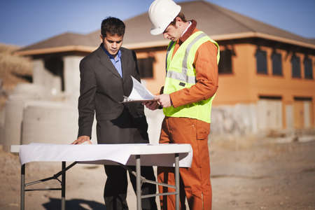 2 men examining plans on worksite LANG_EVOIMAGES