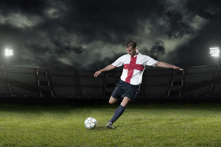 Soccer player kicking ball in pitch LANG_EVOIMAGES