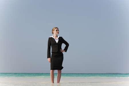 Businesswoman standing on tropical beach