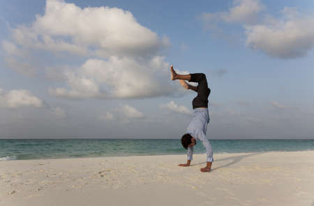 Businessman doing handstand on beach