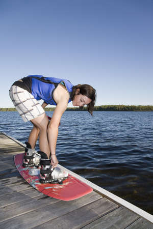 Woman strapping into wakeboard LANG_EVOIMAGES