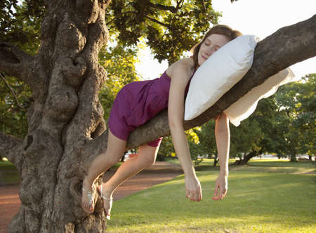 Young woman sleeping on a tree
