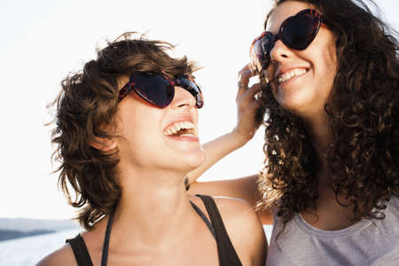 Laughing women in sunglasses on beach