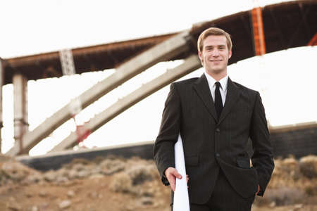 accomplishes: Man in suit on worksite smiling