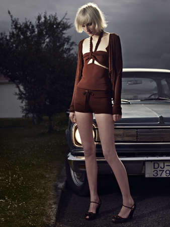 Woman standing by vintage car LANG_EVOIMAGES