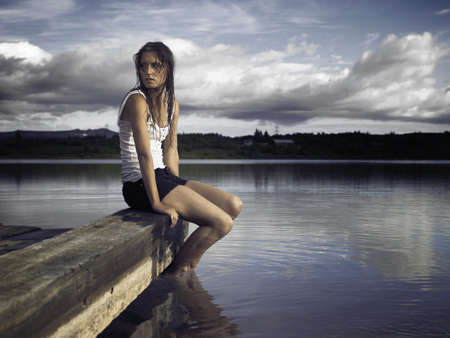 Woman sitting on dock by lake