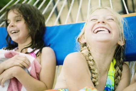 2 young girls laughing in hammock