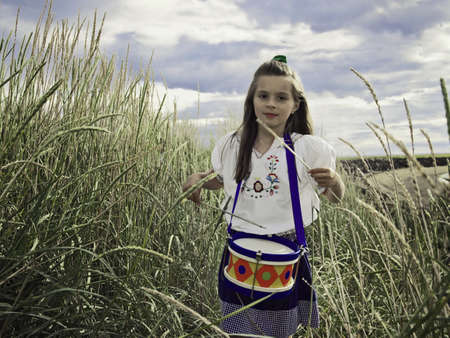 Girl playing with drums in wheat field LANG_EVOIMAGES