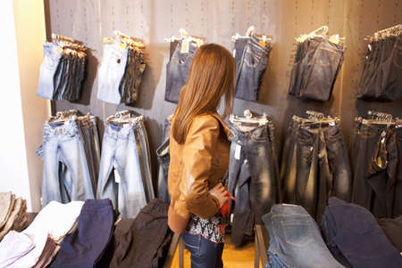 requiring: Girl checking jeans in a clothes shop