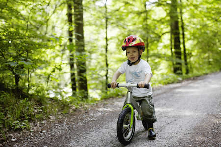 Toddler boy riding bike on dirt path