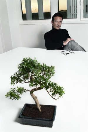 musing: Creative at table musing over bonsai