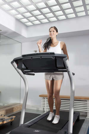 Smiling woman exercising on treadmill LANG_EVOIMAGES