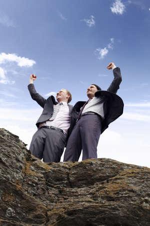 Businessmen cheering on cliff edge LANG_EVOIMAGES