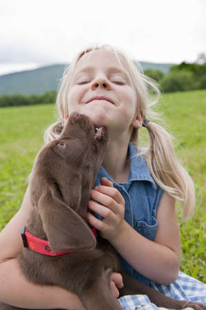 furs: Young girl hugging her puppy