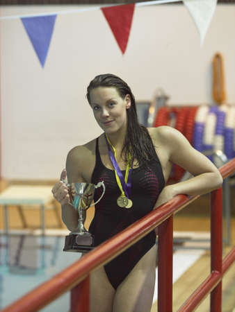 Swimmer holding medals by pool
