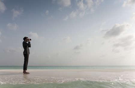 Businessman using binoculars on beach