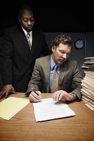 Man at desk with man over shoulder