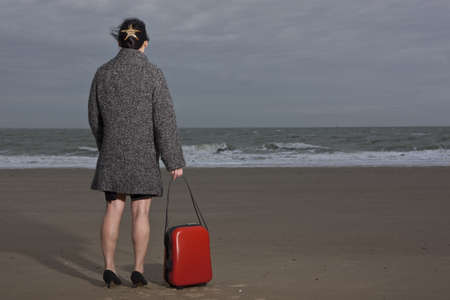 forties: Woman rolling luggage on sandy beach