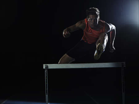 aggressively: Runner jumping over hurdle on track