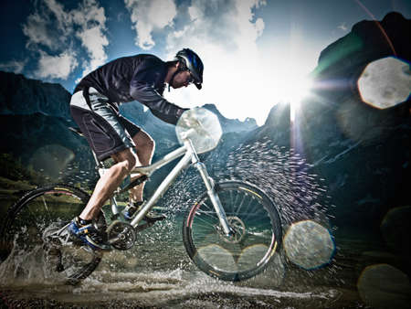 Male mountain biker riding through water