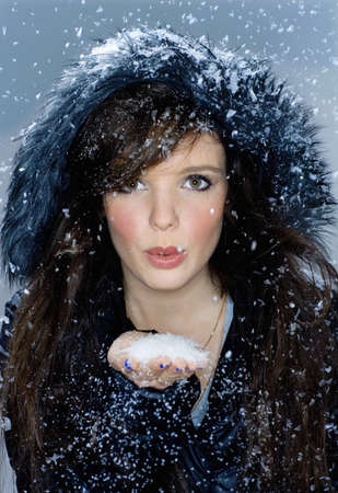 hearted: Portrait woman blows snow from hand