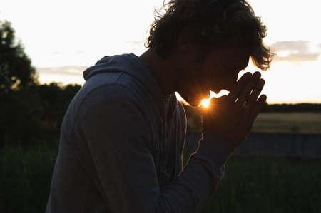 pleading: Silhouette of man praying at sunset