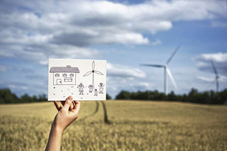 Woman with drawing at wind turbines