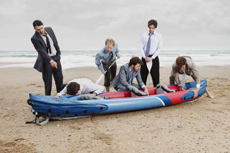survives: Businessmen with canoe on beach LANG_EVOIMAGES