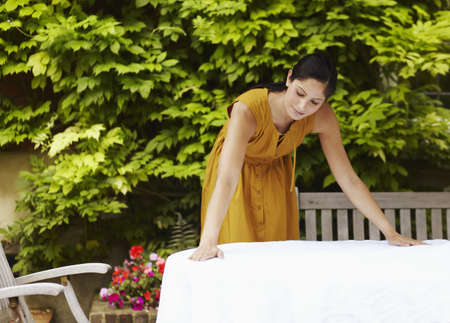 enclose: Woman spreading tablecloth outdoors LANG_EVOIMAGES