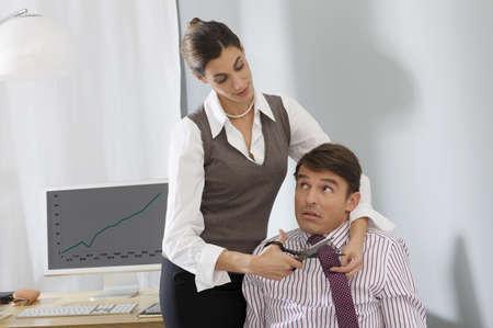 female colleague cutting mans tie LANG_EVOIMAGES