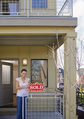 abodes: woman on front porch with sold sign