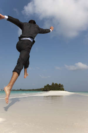 rushed: Businessman jumping on tropical beach