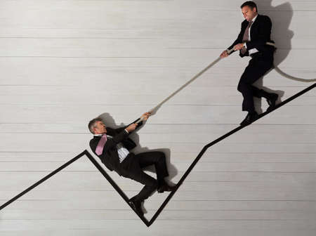 indebted: Business men climbing up graph