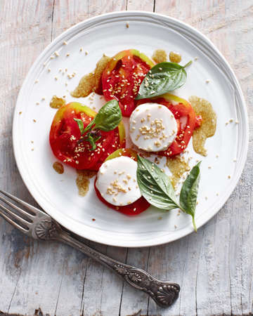 uncomplicated: Plate of tomatoes and cheese on table LANG_EVOIMAGES